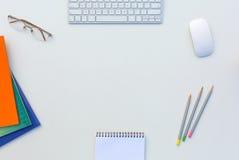 A tabela branca do escritório com cor do rato do teclado de computador escreve brochuras e outro fontes Imagens de Stock Royalty Free