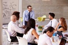 Tabela caucasiano da sala de reuniões de Leading Meeting At do homem de negócios imagens de stock royalty free