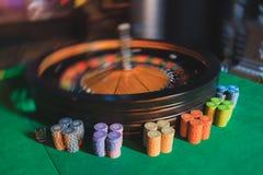 Tabela colorido do casino com roleta no movimento com grupo de jogar povos ricos ricos no fundo Fotografia de Stock Royalty Free