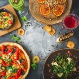 Tabela com alimento do vegetariano - pizza, salada, torta e bebidas na obscuridade Configuração lisa, vista superior Fundo do ali imagem de stock