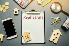 Tabela com casas de madeira, calculadora, moedas, lupa com os bens imobiliários da palavra Comprando e vendendo bens imobiliários foto de stock