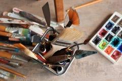 Tabela com ferramentas e pinturas na oficina do artista imagens de stock royalty free
