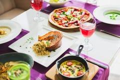 Tabela com pratos de vegetariano - pizza, saladas, sopa, torta e bebidas Alimento no restaurante fotografia de stock