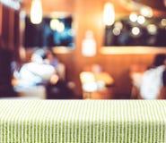 Tabela com toalha de mesa verde do teste padrão com o backgro do restaurante do borrão fotografia de stock