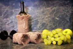 Tabela com a uva da garrafa de vinho foto de stock