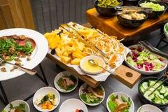 Tabela com a variedade do queijo com mel e vegetais nas saladas imagem de stock