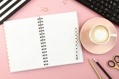 Tabela cor-de-rosa da mesa de escritório com caderno, a xícara de café, a pena, o lápis, as tesouras e o computador abertos fotografia de stock royalty free
