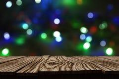 a tabela 3D de madeira rústica contra o bokeh do Natal ilumina o fundo Foto de Stock Royalty Free