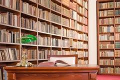 Tabela da biblioteca com a estante no fundo Fotos de Stock Royalty Free