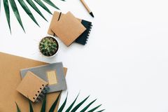 Tabela da mesa de escritório com bloco de notas, fontes e folhas de palmeira do ofício fotografia de stock