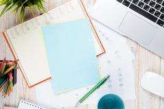 Tabela da mesa de escritório com computador, fontes, copo de café e flor foto de stock