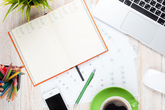 Tabela da mesa de escritório com computador, fontes, copo de café e flor fotografia de stock