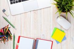 Tabela da mesa de escritório com computador, fontes e flor imagem de stock royalty free