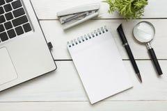 Tabela da mesa de escritório com fontes Vista superior Copie o espaço para o texto Portátil, bloco de notas vazio, pena, lupa, ca Imagem de Stock Royalty Free