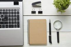 Tabela da mesa de escritório com fontes Vista superior Copie o espaço para o texto Portátil, bloco de notas vazio, pena, lupa e f Fotos de Stock