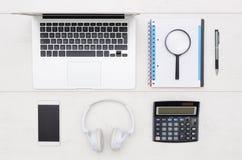 Tabela da mesa de escritório com portátil, smartphone, e materiais de escritório Fotografia de Stock Royalty Free