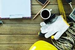 Tabela da oficina de manutenção com ferramentas do equipamento e copos de café imagem de stock