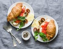 Tabela da refeição matinal ou de café da manhã - croissant com queijo creme e salmão fumado, e tomates de cereja Café da manhã eq imagem de stock