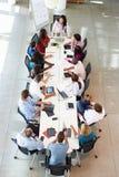 Tabela da sala de reuniões de Addressing Meeting Around da mulher de negócios Fotos de Stock Royalty Free