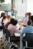 Tabela da sala de reuniões de Addressing Meeting Around da mulher de negócios Fotos de Stock