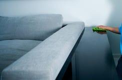 Tabela da varredura da empregada perto do sofá Imagem de Stock Royalty Free