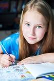 A tabela de assento da menina bonita do retrato com livro para colorir adulto escreve Fotos de Stock