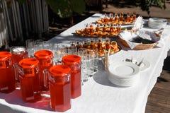 Tabela de banquete de abastecimento belamente decorada com os petiscos e bebidas diferentes do alimento Fotos de Stock Royalty Free