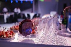 A tabela de banquete da restauração com os petiscos do alimento, os sanduíches, os bolos, os copos e as placas cozidos, saque do  Fotografia de Stock