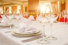 Tabela de banquete do serviço em um restaurante no por do sol Imagem de Stock