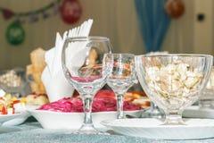 Tabela de banquete servida com fundo borrado no restaurante Vidros de vinho vazios, salada dos vegetais e close up cortado do fru Imagem de Stock Royalty Free