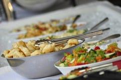 Tabela de bufete connosco do alho e salada do jardim com tenazes de brasa do serviço Imagens de Stock