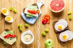 Tabela de café da manhã com sanduíches do queijo, salsicha, vegetais, os ovos cozidos duros e os frutos foto de stock royalty free