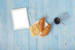 Tabela de café da manhã com café, tabuleta, croissant, queijo, doce, a foto de stock