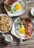 Tabela de café da manhã completa - ovos fritos com bacon e batatas, ervilhas verdes, panquecas do alho-porro em uma tabela de mad Imagem de Stock