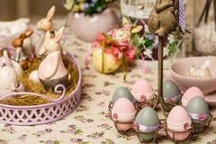 A tabela de café da manhã da Páscoa com chá, ovos em uns copos de ovo, mola floresce no vaso e na decoração da Páscoa Imagem de Stock