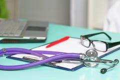 Tabela de funcionamento do espaço de trabalho do ` s do doutor com formulário paciente do papel vazio da descarga do ` s, prescri imagem de stock