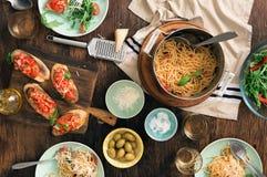 Tabela de jantar italiana com massa, bruschetta e salada fotos de stock royalty free