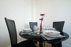 A tabela de jantar moderna setup com flores Foto de Stock