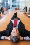Tabela de Lying On Conference do homem de negócios foto de stock