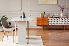 Tabela de mármore ao lado de uma cadeira em uma sala de jantar eclético com um armário retro fotos de stock