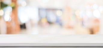 Tabela de mármore branca vazia sobre o fundo da loja do borrão, bandeira, montagem da exposição do produto imagens de stock royalty free