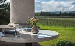 Tabela de mármore com ajustes do jantar e vaso de flor sobre o vinhedo fotografia de stock