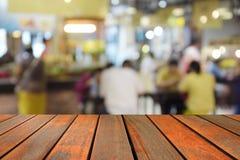 Tabela de madeira borrada da imagem no centro do alimento no shopping e no peo Imagem de Stock