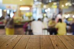 Tabela de madeira borrada da imagem no centro do alimento no shopping e no peo Imagens de Stock