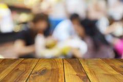 Tabela de madeira borrada da imagem no centro do alimento no shopping e no peo Fotografia de Stock