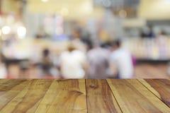 Tabela de madeira borrada da imagem no centro do alimento no shopping e no peo Foto de Stock Royalty Free