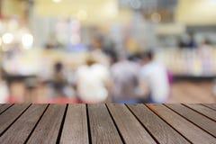 Tabela de madeira borrada da imagem no centro do alimento no shopping e no peo Fotos de Stock Royalty Free