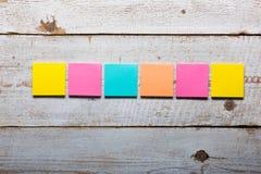 Tabela de madeira branca com notas pegajosas coloridas vazias Fotos de Stock Royalty Free