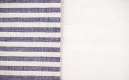 Tabela de madeira branca com uma toalha de mesa listrada azul imagem de stock