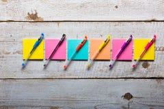 Tabela de madeira branca retro com notas pegajosas coloridas vazias Fotografia de Stock Royalty Free
